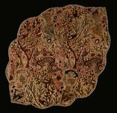 مردی (اسکندر؟) در تلاش برای کشتن اژدها، با تکرار متناوب نقش در موقعیت معکوس، یک قطعه پارچه مخمل، یزد (؟)، اواسط سده ۱۶ ترسایی، صفوی، گمان میرود این قطعه پارچه باقی مانده غنایم جنگی باشد که از ارتش ترکیه در محاصره شهر وین در سال ۱۶۸۳ ترسایی بدست آمده است. Fragmento de tecido Pérsia, Yazd (?), meados do século XVI Este fragmento de veludo policromo, em forma de medalhão oval, de contornos lobados, representa Iskandar (Alexandre, o Grande), tentando mata...