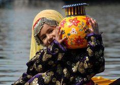 Kashmiri girl with cultural dress and pot.