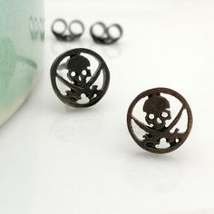 Black skull and sword circular stud earrings for men. These skull cut out earrings are made from sterling silver and plated in black gold. Sold as a