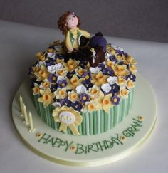 This is the 60th birthday cake I made for my friend's mum. A little horse and rider standing in a field of purple and yellow spring flowers with a few daffodills.