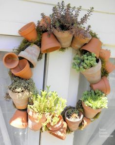 Herb wreath: mini terracotta pots wired together through their drainge holes. Upright pots then filled with dirt and plants.