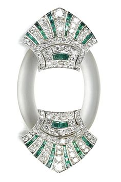 Rock crystal, emerald and diamond brooch, Janesich, circa 1925. Of oval form, the carved rock crystal decorated at each side with triangular terminals millegrain set with circular- and single-cut diamonds alternating with calibré-cut emeralds, signed Janesich Paris and numbered.