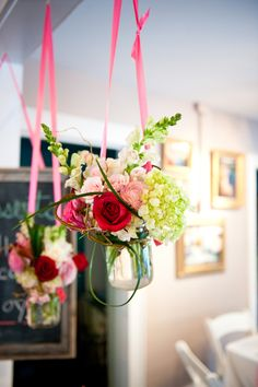 Mason jars full of fall looking flowers with a colored cloth napkin underneath and a ribbon around the jar.