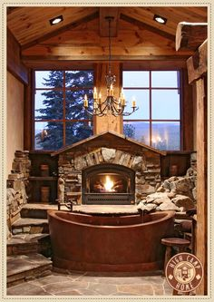 This is a stunning bathroom with a copper tub and field stone everywhere to bring the outside in. The dancing fire with the two windows overlooking high into the trees and mountains adds a truly cozy feel to this rustic bathroom. | Caption by Jenn Brown