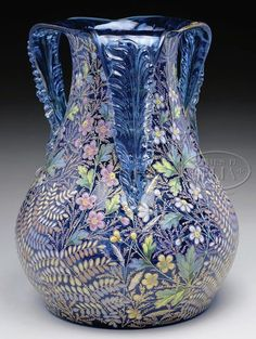 A Moser glass vase decorated with brightly enameled flowers, stems and leaves encircling the entire vase. The decoration is set against a beautiful aqua-blue background. The vase is finished with three handles that are pulled from the lip and attached to the side. Each blue handle has an applied clear glass leaf decoration, Czechoslovakia, circa 1875-1925