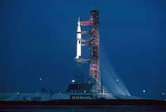 """The Milkstool Xenon floodlights illuminate the twenty-two-story-tall Skylab 3 Saturn IB and Launch Umbilical Tower (LUT) at Pad 39B at dusk on July 27, 1973. This angle looks west. Within hours, the launch vehicle would be fueled for the second time in eight days; the first, on July 20, was part of the combined countdown and countdown demonstration test (CDDT). The Holloway Corporation of Titusville, Florida, built the """"milkstool"""" pedestal."""