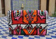 Gorgeous clutch bag made of colorful Moroccan fabric , happy colors and soft feeling .  the bag has a pocket inside and comes with a detachable metal chain . Dimensions : 28 cm x 18 cm ( 11 x 7  ) Please feel free to contact me if you have any questions .