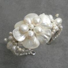 @Overstock - Indulge on this refined piece of jewelry that features stunning flower made of white mother of pearl. This cuff bracelet also features freshwater pearl stones and was handmade in Thailand by artisan Lai.  http://www.overstock.com/Worldstock-Fair-Trade/Cute-White-Shell-Flower-and-Pearl-Beaded-Cuff-7-20-mm-Thailand/5601229/product.html?CID=214117 $33.99