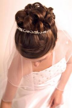 This updo is an elegant look that goes well with a tiara and a veil. This wedding hairstyle stays the same throughout the day's events, so you don't have to stress about it. Bride's hair has a suble side part with loose curls pinned up in a clasic bridal updo. Tiara is thin and worn at the top of the curls, the viel is placed directly below base if the curls.