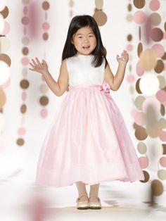 Sleeveless satin and organza tea-length A-line dress with jewel neckline, thin satin set-in waistband with side flower and bow accent, covered buttons down back bodice, organza overlay skirt accented with double band at hemline.#timelesstreasure