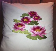 A cushion with machine embroidery lotus flower designs.