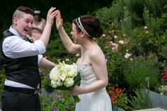 Newlyweds high five in the Perennial Border at Toronto Botanical Garden #Toronto #Garden #Wedding