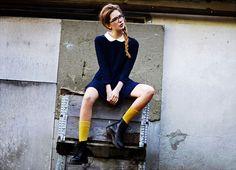美人の要素って一体なに?顔?髪型?性格?きっとすべてが当てはまるけれど、日常で忘れがちなポイントは足元。靴と洋服のバランス、靴下やストッキングの色使いなどきちんと考えていますか?世界中に潜む美人たちが足元のおしゃれを教えてくれます! エバさん・19歳・スウェーデン、ウメオ市在住 黄色い縫い目が目印のドクターマーチンのショートブーツを知らない人はいないでしょう。しかしドクターマーチンといえば、女性にとってはパンクで、ハードなイメージがありますよね。1960年代から90年代の間にパンクやニュー・ウェーブなどのサブカルチャーの間で流行ったからでしょうか。 そんな印象をまるで存在しないかのように崩したのがエバさんのルックス。まずは黒縁メガネと丸襟の紺色ワンピースでスクールガールっぽい真面目さと少女らしさを表現。足元にはブーツの縫い目を意識して、同色のクルーソックスを選んでいます。このソックスこそがスタイリングのポイント。黄色いアクセントがなければ「人気のドクターマーチンを履いてみたかった、お利口な少女」で終わってしまうでしょう?いいえ、エバさんの組み合わせはすべて考えつくしたもの...