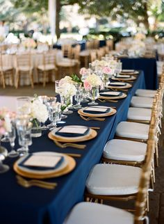 Navy tablecloths with a gold charger, gold-rimmed white plates, navy napkins, custom menus. Crystal vases with blush flowers alternating with gold filigree votives and glass pillars with floating candles