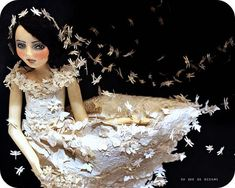 """Brighid, the Wind's Bride"""" is wearing a veil of paper dragonflies and a dress made of embossed decorative paper embellished with paper dragonflies, butterflies, leaves and blossoms"""