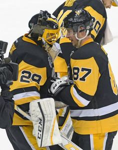 Pittsburgh Penguins center Sidney Crosby (87) congratulates goalie Marc-Andre Fleury (29) after an NHL hockey game against the New Jersey Devils, Friday, Dec. 23, 2016, in Pittsburgh. (AP Photo/Fred Vuich)