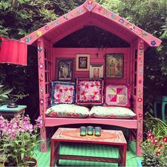 """""""My gazebo has had a makeover #woodlandparty #MWwoodland"""" As snapped by Matthew Williamson on Instagram. A pink painted gazebo decorated with patterned cushions and art work in the corner of a garden with flowers"""
