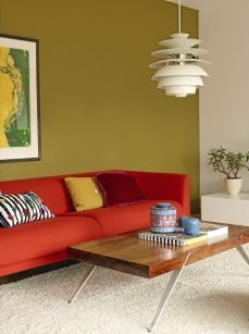 Beautiful green wall with red sofa, minimalistic vintage