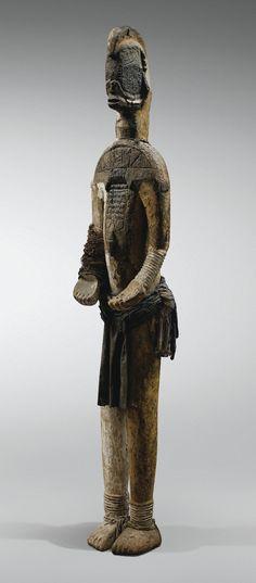 Statue, Igbo - . Leur disposition au sein du sanctuaire, de même que leurs dimensions respectives, hiérarchisaient leur importance. Ici, la monumentalité de la sculpture l'identifie sans aucun doute à une divinité tutélaire alusi - autour de laquelle étaient disposées les effigies ancestrales.