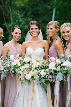 bridesmaids in purple with organic overflowing bouquets.