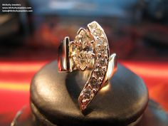Unique marquise and round diamond ring, in yellow gold. McNulty Jewelers original design