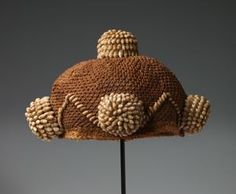 "Mbala peoples Creation Place/Dates:Democratic Republic of the Congo, 20th century Title:Chief's Hat (""Mpu a nzim"") Medium:Raffia fiber and snail (nsimbu) shells Dimensions:5 7/8 x 10 13/16 x 10 13/16 in. (15 x 27.5 x 27.5 cm) , 5-7/8 x 10-13/16 x 10-13/16 in. , 15 x 27.5 x 27.5 cm"