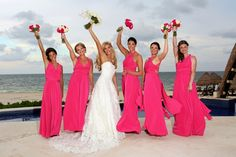 Love these long hot pink bridesmaid dresses! Perfect for a beach wedding.