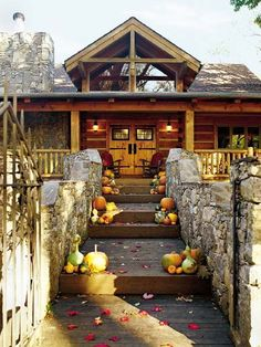 This rustic fall cabin home resembles an inviting lodge with a wraparound porch; an angled, sloping roof; and a prominent front dormer with large window.