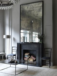 Grey walls with an antique mirror over a black fireplace contrast with a modern coffee table designer Erin Swift http://www.homebarnshop.co.uk/