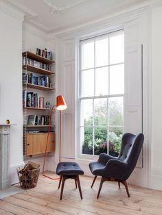 coin lecture chaleureux à côté de la fenêtre, aménagé avec un fauteuil et un repose pieds en gris anthracite, un lampadaire orange et un meuble bibliothèque mural