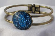 Superbe bracelet en métal bronze, monté d'un cabochon de verre de 25mm de diamètre avec motifs mandala bleu Taille du bracelet : 20 cm (le bracelet s'ouvre en deux derriere le cabochon) Ne pas mouiller le bracelet