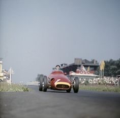 This marvelous color image shows Juan Manuel Fangio braking for the South Curve complex shortly after the start/finish line on the old Nürburgring during the famous German Grand Prix of August 4, 1957. This photograph was taken early in the race while Fangio built up an initial lead with his Maserati 250F over the Ferrari 801s of Peter Collins and Mike Hawthorn.