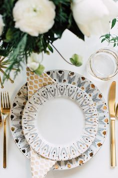 We love how sharp and classy the Kate Spade brand is.  Often associated  with bright pops of color, we decided to interpret the brand with New  Years in mind.  Metallics and bright whites made up the palette for this  setting.Add a little fun by mixing prints with the Ikat plates from Anthropologie and the gold printed pattern from the West Elm napkins.  Gold flatware from West Elm played off the gold rimmed glass also from Anthropologie.  The all white blooms reminded me of snow and didn't…