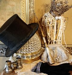 A Vintage New Year. An antique beaver fur top hat is complimented by an old mother of pearl umbrella handle, silver opera glasses, a pair of black ladies gloves, and a trophy spilling over with pearls and a french jeweled crown.