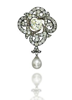 A 19TH CENTURY DIAMOND AND NATURAL PEARL BROOCH  Centering upon a cushion-shaped diamond of yellowish tint, to the diamond-set scrolling surround, suspending a detachable drop-shaped natural pearl, measuring approximately 10.1-11.0 x 13.0 mm, mounted in silver and gold, late 19th Century