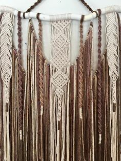 This large macrame wall hanging is a true statement piece! It is made with cotton twine and yarn and is hung on a piece of curvy white wood. The yarn is shades of brown and beige with little flecks of colour throughout. It is hand made and ready to ship! Measurements Width of