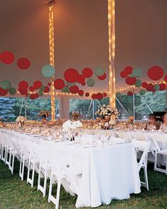 The couple found an inexpensive way to decorate a large tent: Paper lanterns in the wedding's colors hang over long banquet tables; strings of lights, along with scores of white votive candles, brighten the space as evening falls.