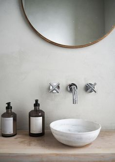 A beautiful neutral bathroom with a round wooden mirror by Frama Copenhagen