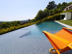 Le débordement par l'esprit piscine - 15 x 4 m Revêtement gris anthracite Plage immergée de chaque coté de l'escalier central Margelles en pierres bleues
