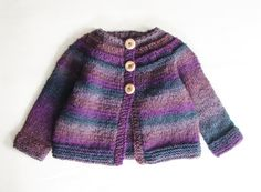 This cardigan will fit baby girls up to one year old.    Hand knitted from soft purple ombre self striping wool blend yarn, this sweater