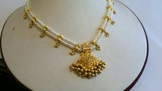 Two Layered Pearl Necklace which has gold design with gold beads suspended in between. And has gold pendant suspended with gold beads.