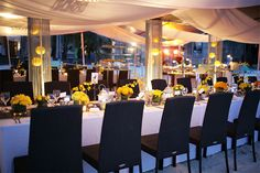The floral centerpieces – shells, yellow flowers (cymbidiums, Holland mums, spider mums) in clear vases. Hand-made candleholders provided soft glow on the tables.