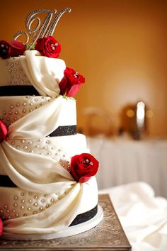elegant black and white wedding cake with red roses, and, of course, the monogram topper