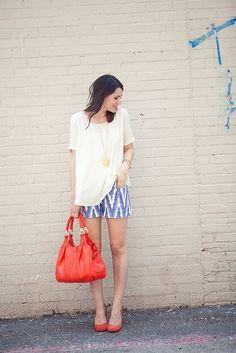 Un short de diseño azul con blanco una camisa larga blanca y una cartera roja