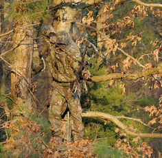 One of the Realtree camo patterns in action: A hunter wearing Realtree APG ™ camo stands in a tree stand and takes aim with his compound bow, amidst dry brown leaves and green pine boughs.