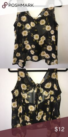 See through floral tank top See through black floral tank top. Perfect to pair with a lace bralette! The back has a bow tie along with a stylish opening right below it (picture 2). It's a large but can fit medium as well. 100% polyester. Tops Tank Tops