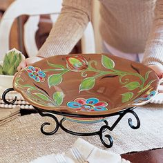 Warm brown contrasts beautifully with cool blue in this set, generously sized for serving. You'll love the extra details on the Cottage Garden Bowl, like the colored bands ringing the base. The Ornate Iron Stand (included) lifts the bowl to add height to a buffet or to display as a decorative element in any room. Gorgeous piece!!   NOTE: Willow House is currently liquidating $30M worth of inventory from our Style for Home Division to focus on our Jewelry Division. Home decor items are…