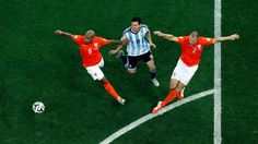Nigel de Jong and Ron Vlaar of the Netherlands compete for the ball with Lionel Messi of Argentina
