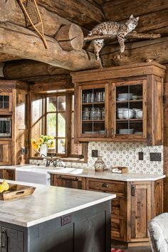 In Vail, Colorado, this log home got the custom touch. A dark gunmetal stain with a crackle and worm-track finish was created for the island and handmade hutch. Brazilian quartzite La Terre Deco tile from Exquisite Surfaces and a cus Log Cabin Kitchens, Log Cabin Homes, Rustic Kitchens, Log Cabins, Kitchen Interior, Kitchen Decor, Kitchen Ideas, Kitchen Planning, Rustic Kitchen Design