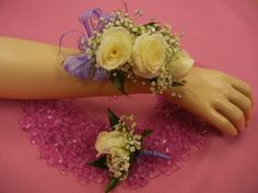 Flowers By Frances: White sweethear roses with baby's breath, opaque quintetts, and purple ribbon. Corsage and matching boutonniere designed using customers ideas.